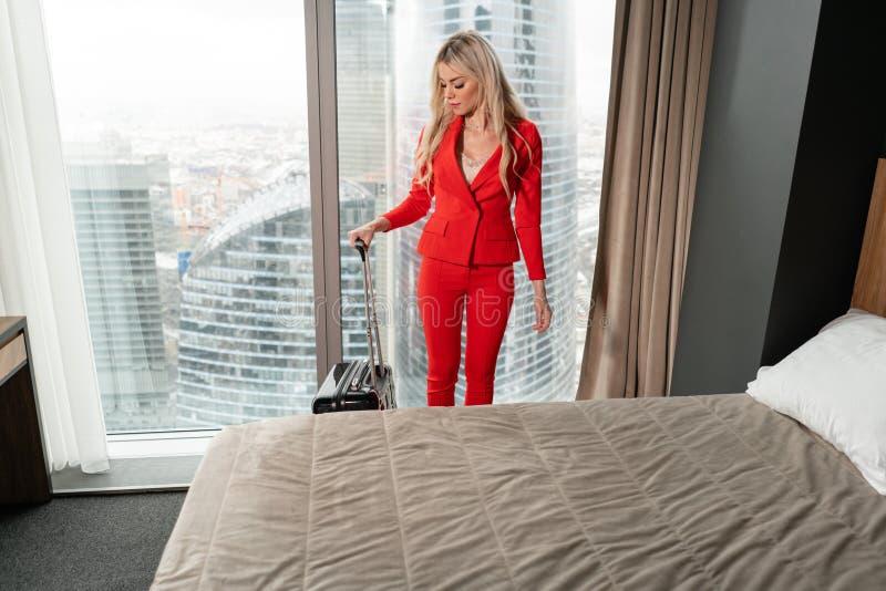 De jonge blonde onderneemster komt in een hotelruimte aan met zwarte koffer E Jong meisje royalty-vrije stock afbeeldingen