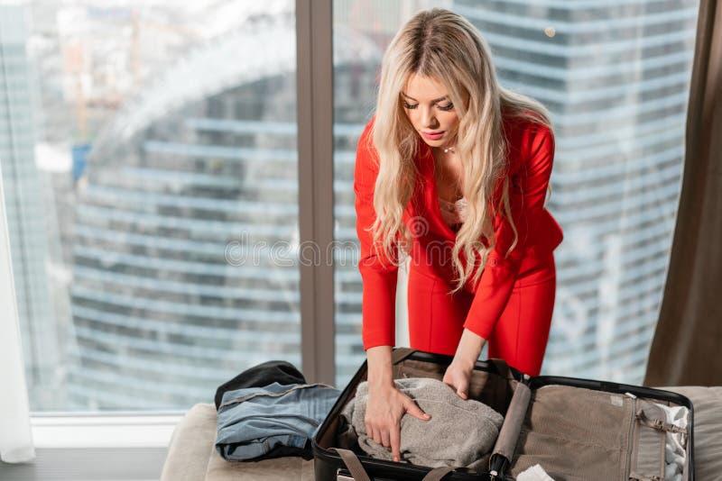 De jonge blonde onderneemster komt in een hotelruimte aan met zwarte koffer E Jong meisje stock afbeelding