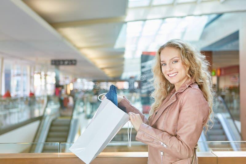 De jonge blonde vrouw is gelukkig over haar aankopen stock afbeelding