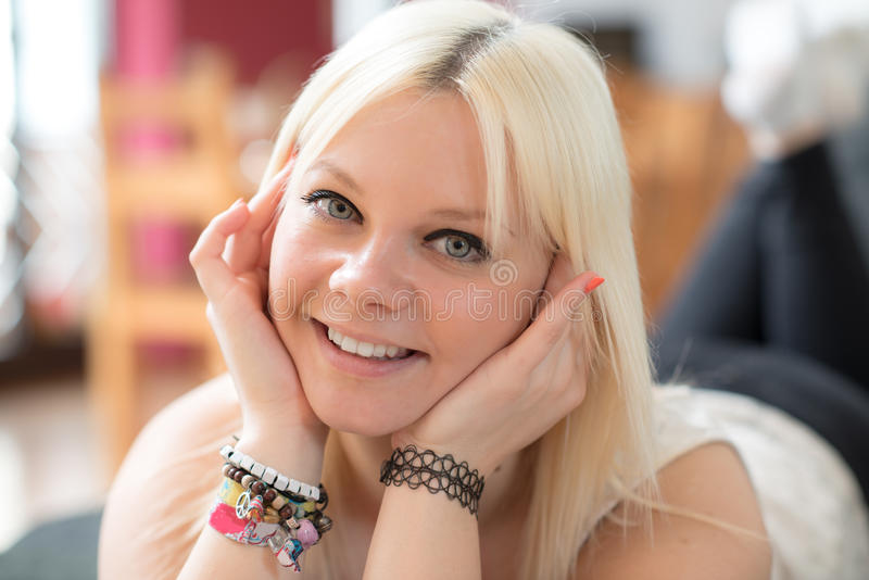 De jonge blonde vrouw glimlacht stock fotografie
