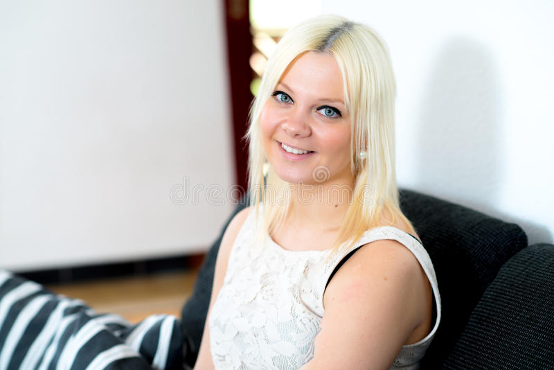 De jonge blonde vrouw glimlacht stock foto's