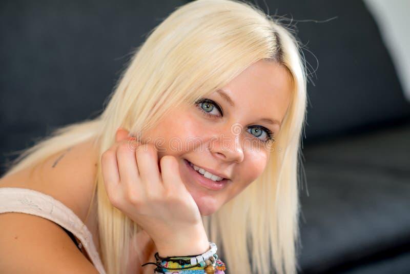 De jonge blonde vrouw glimlacht royalty-vrije stock afbeeldingen