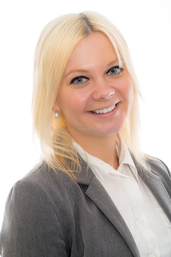 De jonge blonde vrouw in grijs jasje glimlacht royalty-vrije stock foto