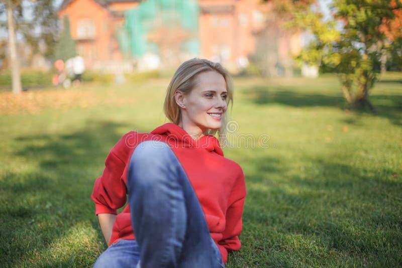 De jonge blonde vrouw zit op het gras in het park Zij is uit koelend stock foto's