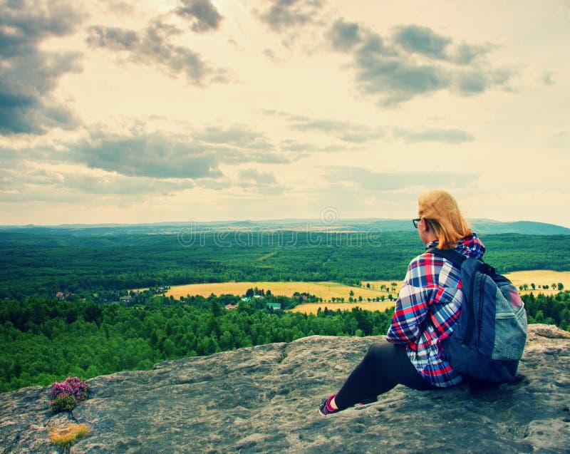 De jonge blonde wandelaar van de haarvrouw neemt een rust op piek van de Berg royalty-vrije stock fotografie