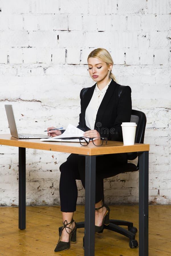 De jonge blonde zitting van de schoonheidsonderneemster bij een bureaulijst met laptop, notitieboekje en glazen in kostuum Bedrij stock afbeeldingen
