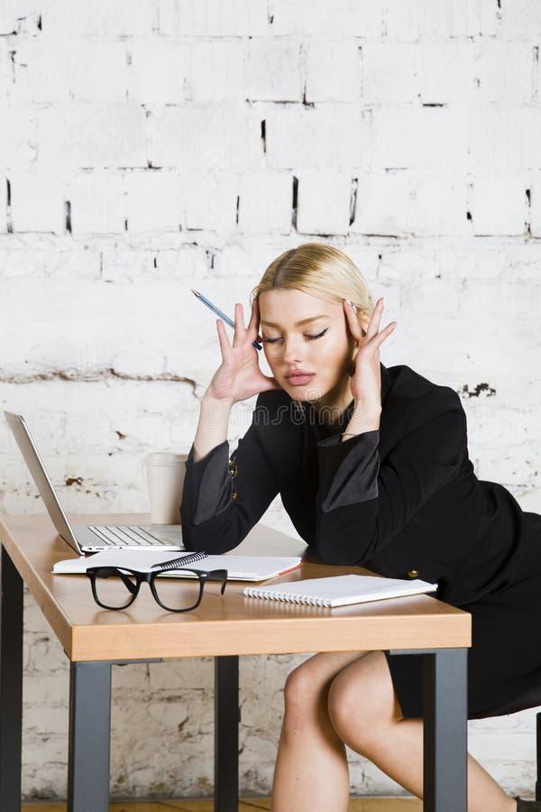 De jonge blonde zitting van de schoonheidsonderneemster bij een bureaulijst met laptop, notitieboekje en glazen in kostuum Bedrij stock afbeelding