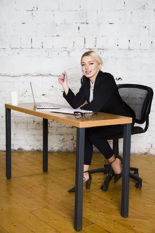De jonge blonde zitting van de schoonheidsonderneemster bij een bureaulijst met laptop, notitieboekje en glazen in kostuum Bedrij stock fotografie