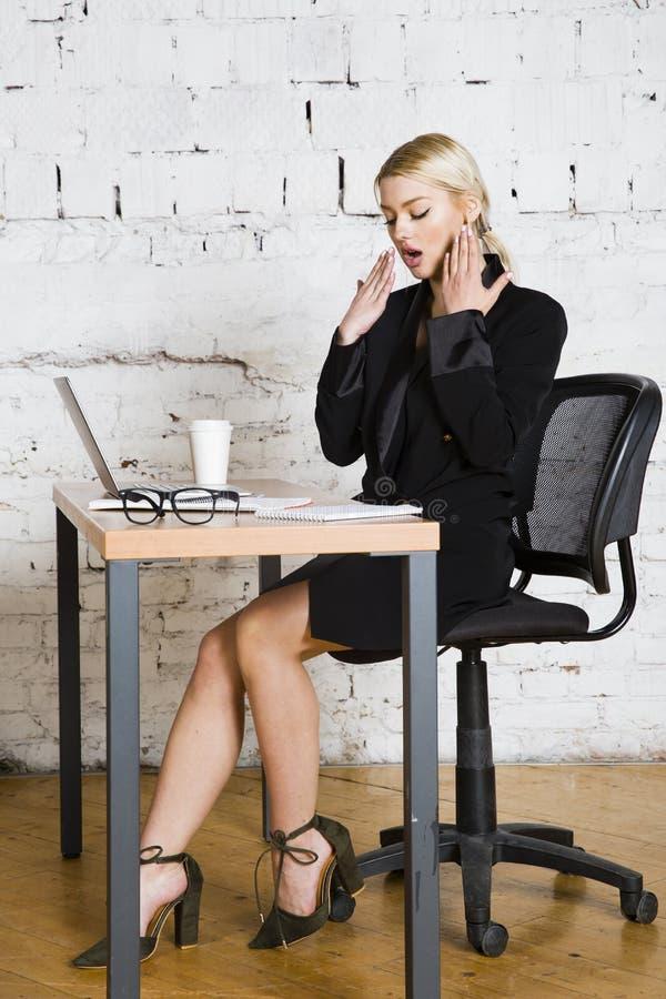 De jonge blonde zitting van de schoonheidsonderneemster bij een bureaulijst met laptop, notitieboekje en glazen in kostuum Bedrij stock foto
