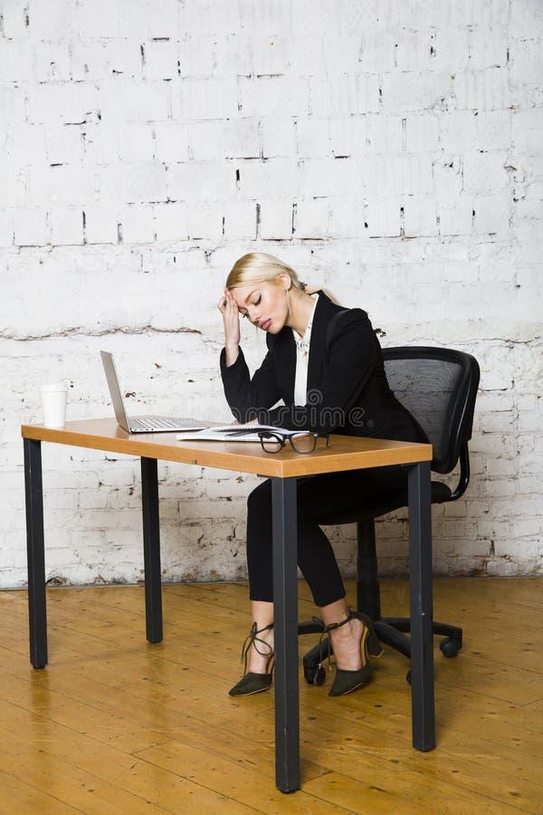 De jonge blonde zitting van de schoonheidsonderneemster bij een bureaulijst met laptop, notitieboekje en glazen in kostuum Bedrij royalty-vrije stock afbeeldingen