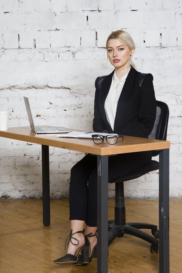 De jonge blonde zitting van de schoonheidsonderneemster bij een bureaulijst met laptop, notitieboekje en glazen in kostuum Bedrij stock foto's