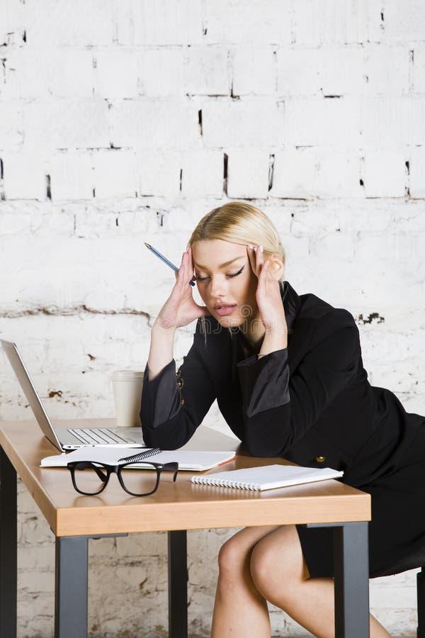 De jonge blonde zitting van de schoonheidsonderneemster bij een bureaulijst met laptop, notitieboekje en glazen in kostuum Bedrij royalty-vrije stock afbeelding