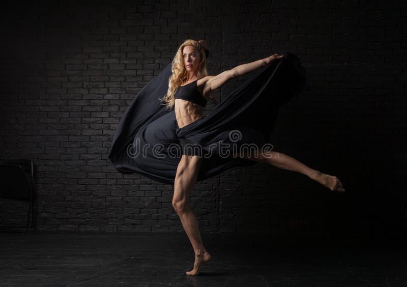 De jonge blondeballerina in sportkledingsondergoed danst en springt in een studio met zwarte baksteen op de achtergrond Modern ba royalty-vrije stock foto's