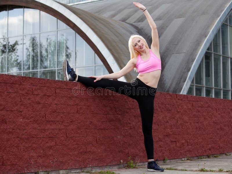 De jonge blondevrouw doet in openlucht hurkzit royalty-vrije stock afbeeldingen