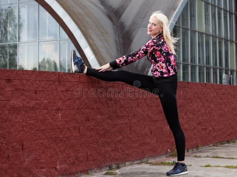De jonge blondevrouw doet in openlucht hurkzit royalty-vrije stock fotografie