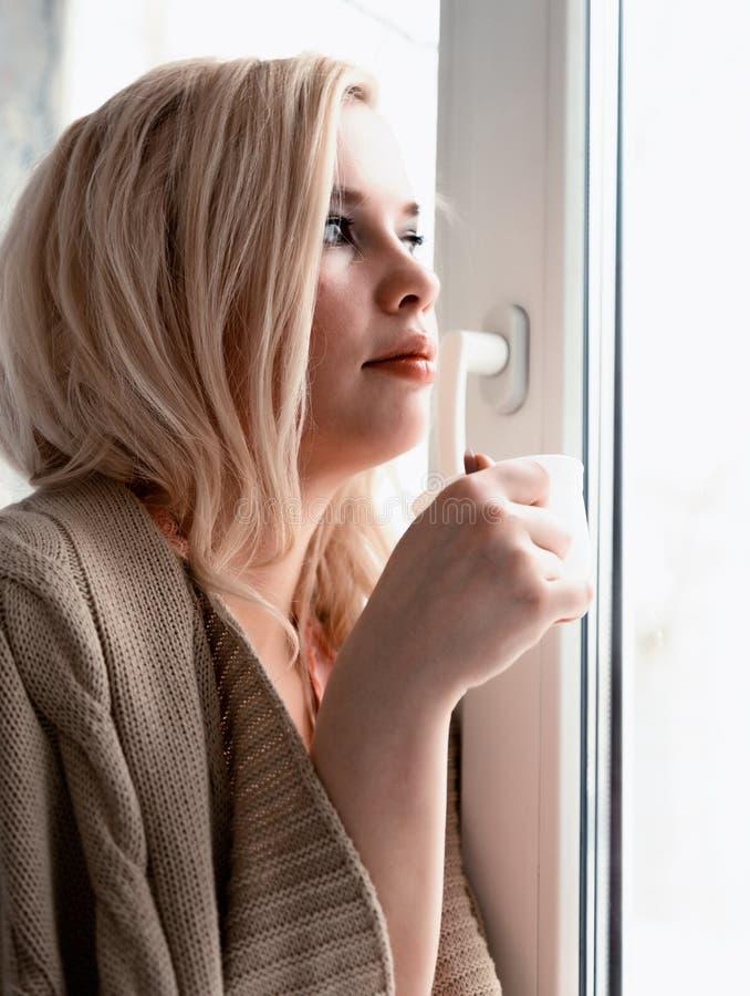 De jonge blondevrouw droomt over iets terwijl het zitten op de vensterbank zij die een thee kop en het drinken houden royalty-vrije stock fotografie