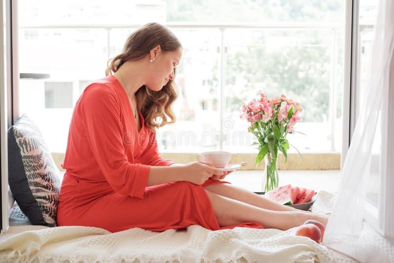 De jonge Blondevrouw in een rode robe drinkt koffie tegen brede winst royalty-vrije stock foto