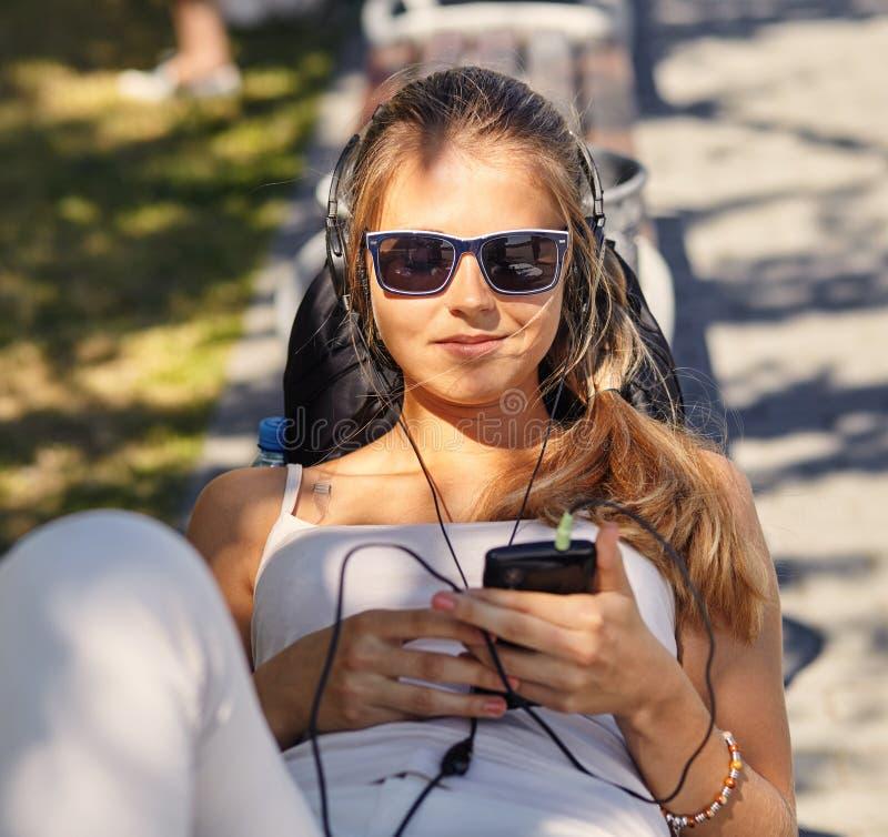 De jonge blondevrouw ligt, geniet de zomer van dag, bloggs en de praatjes via smartphone, draagt in schaduwen, heeft positieve gl royalty-vrije stock fotografie