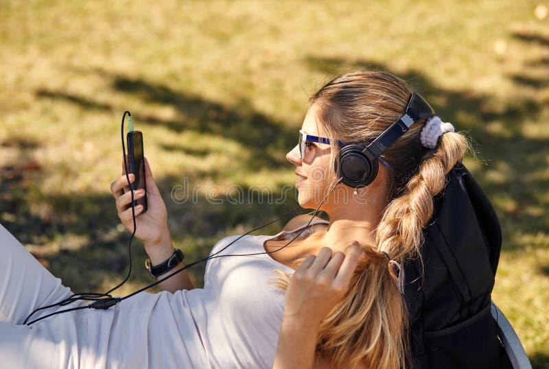 De jonge blondevrouw ligt, geniet de zomer van dag, bloggs en de praatjes via smartphone, draagt in schaduwen, heeft positieve gl royalty-vrije stock afbeeldingen