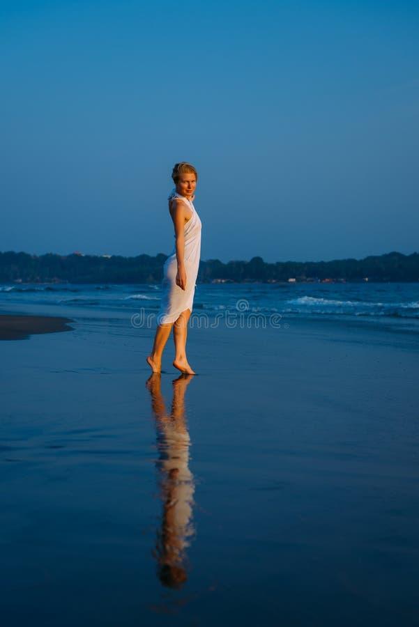 De jonge blondevrouw loopt blootvoets langs de branding op het overzees op een warme de zomeravond Zacht licht bij zonsondergang, stock afbeelding