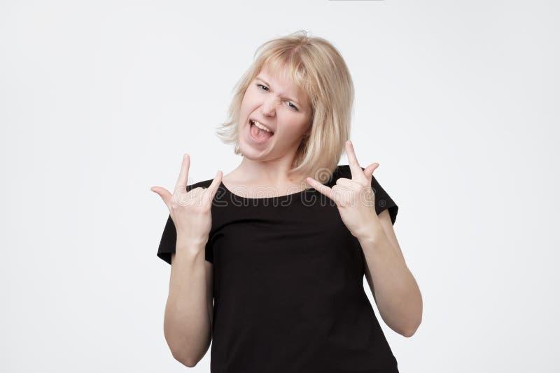 De jonge blondevrouw maakt het gebaar van het rotsn broodje, luistert zwaar metaal, luid uitroept royalty-vrije stock afbeelding