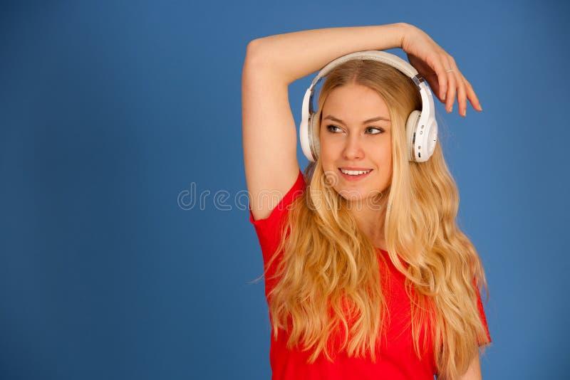 De jonge blondevrouw met hoofdtelefoons luistert aan de muziek over blauwe achtergrond royalty-vrije stock afbeelding