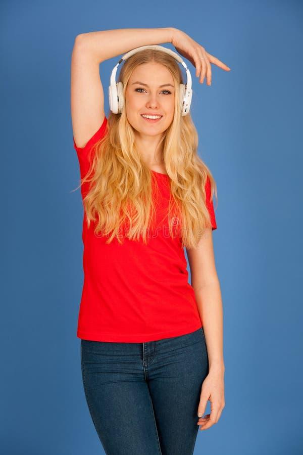 De jonge blondevrouw met hoofdtelefoons luistert aan de muziek over blauwe achtergrond royalty-vrije stock foto's