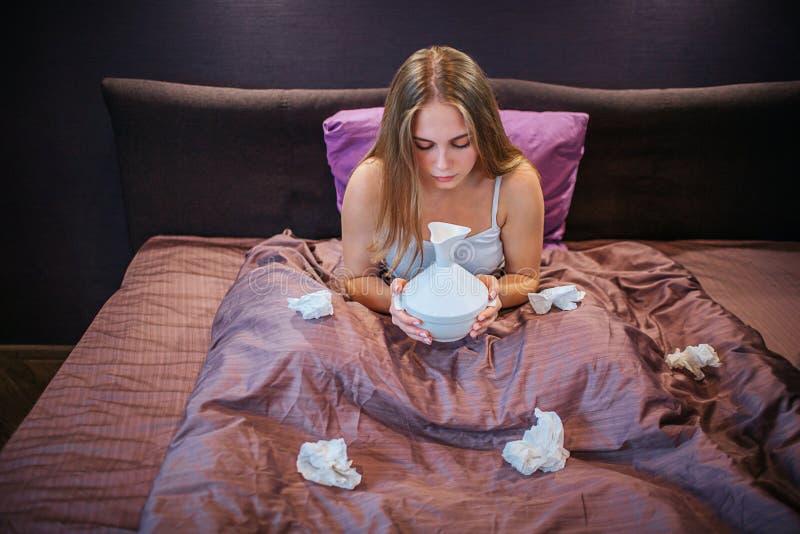 De jonge blondevrouw zit op bed Zij houdt inhaleertoestel en kijkt neer op het Er zijn partijen op gebruikte witte weefsels op be royalty-vrije stock afbeeldingen