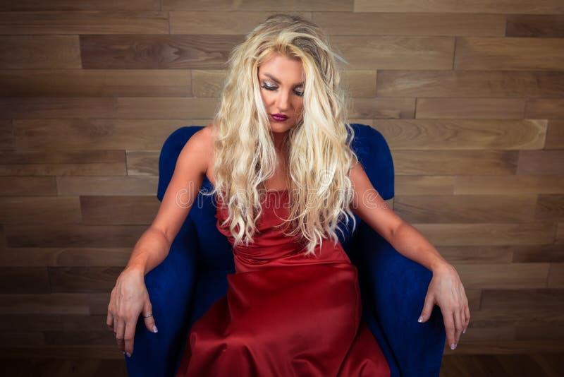 De jonge blondevrouw zit op leunstoel Peinzend meisje in elegante rode kleding royalty-vrije stock afbeelding