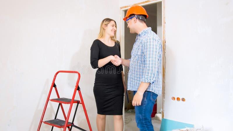 De jonge bouwvakker en het mooie onderneemster schudden dienen in aanbouw huis in royalty-vrije stock afbeeldingen