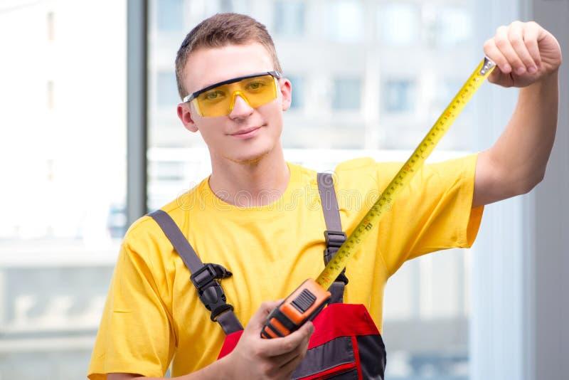De jonge bouwvakker in gele overtrekken stock foto's
