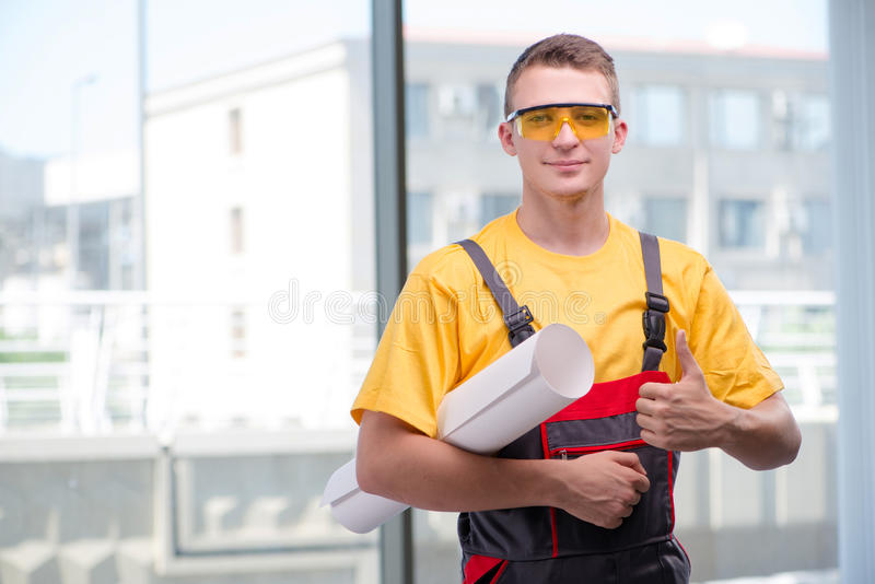De jonge bouwvakker in gele overtrekken stock foto