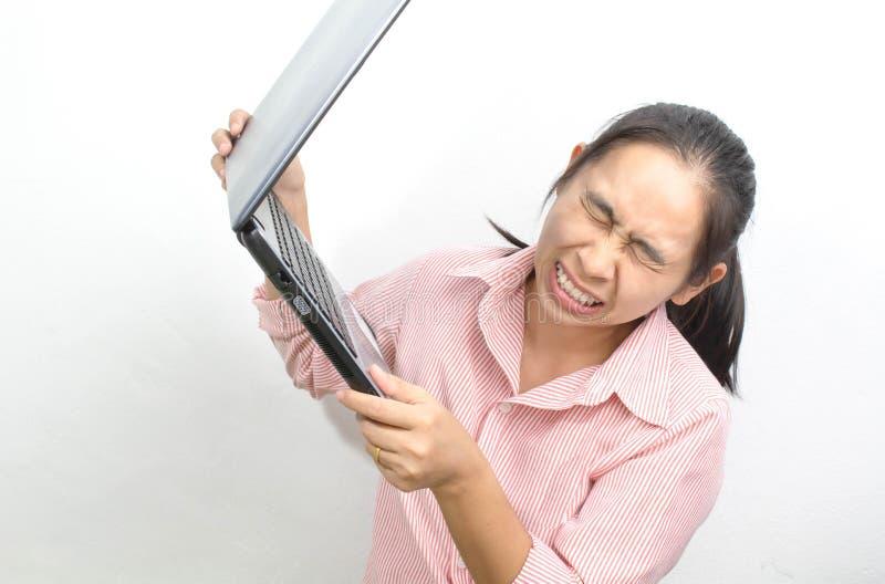De jonge boze Aziatische vrouw de open mond die opheffend laptop tot het gillen werpt isoleerde weg op een witte achtergrond royalty-vrije stock afbeelding
