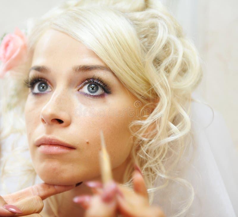 De jonge bruid die huwelijk doet maakt omhoog stock foto's