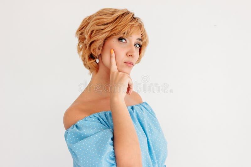De jonge charmante denkende vrouw van het blonde korte haar in blauwe die de zomerkleding, op witte achtergrond wordt geïsoleerd royalty-vrije stock fotografie