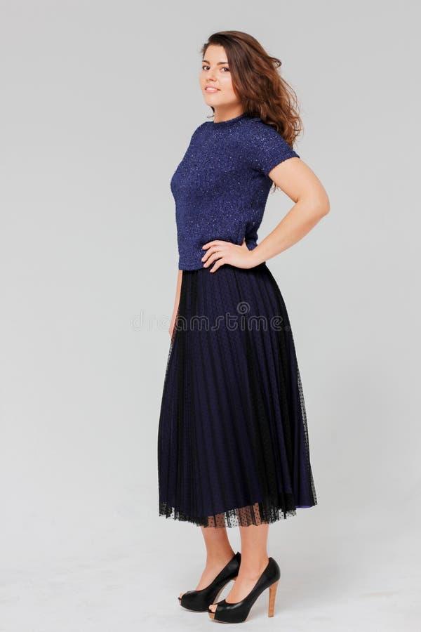 De jonge charmante donkerbruine vrouw met krullend haar in elegant gelijk maken kijkt stock fotografie