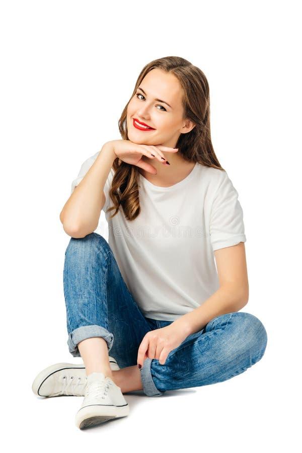 De jonge cherful vrouw in jeans, witte t-shirt, tennisschoenen zit op de vloer en glimlacht Geïsoleerdj op witte achtergrond royalty-vrije stock afbeelding