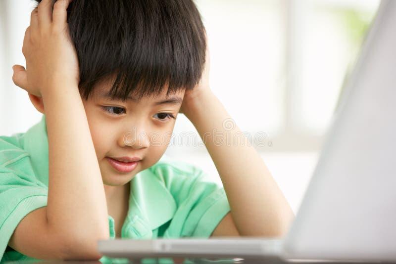 De jonge Chinese Zitting die van de Jongen Laptop thuis met behulp van stock foto's