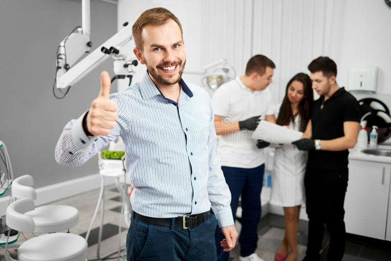 De jonge cliënt van een tandheelkunde glimlacht aan de camera en toont duimen die omhoog gelukkig na de behandeling zijn royalty-vrije stock foto's