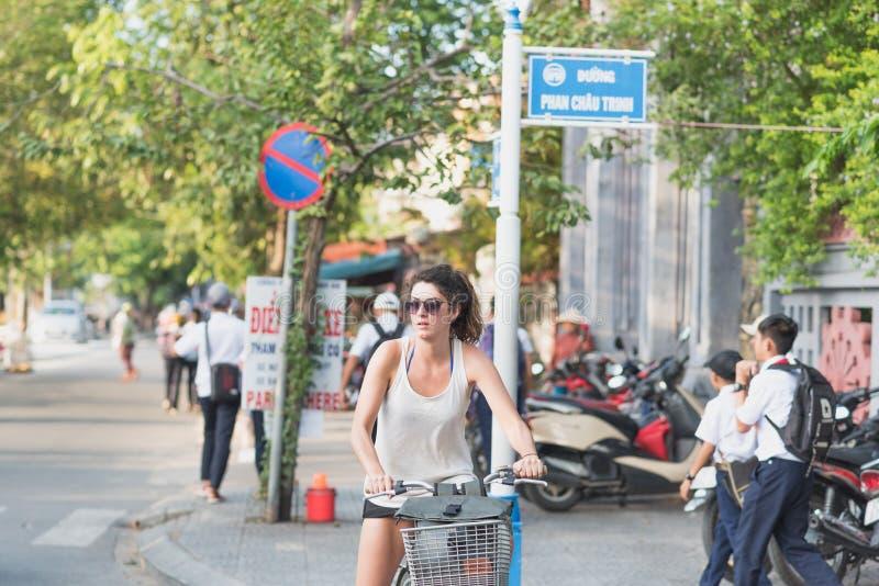 De jonge cycli van de vrouwenreiziger in Hoi An stock afbeeldingen
