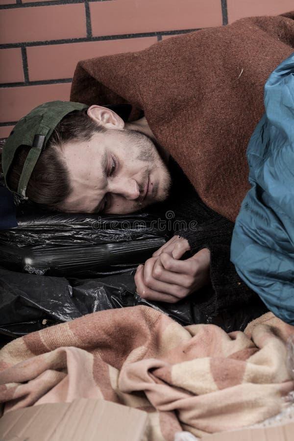 De jonge dakloze mens wordt gestenigd stock fotografie