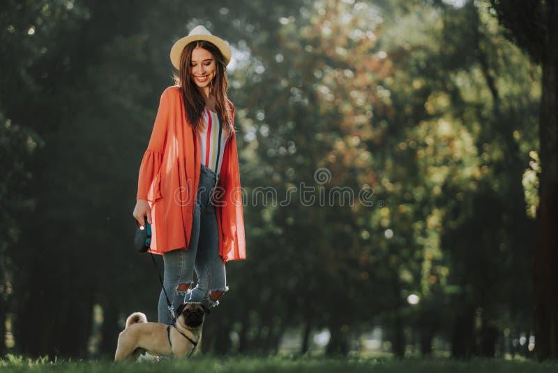 De jonge dame bevindt zich in park met haar hond stock foto's