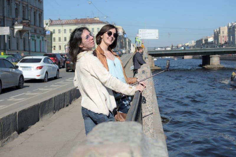 De jonge damestoeristen in Heilige Peteresburg Rusland genieten van de zomer op een zonnige dag en begroeten sightseeingsboten stock afbeeldingen
