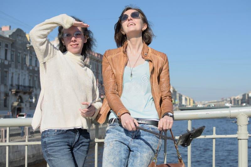 De jonge damestoeristen in Heilige Petersburg Rusland nemen selfies op een houten brug in het historische stadscentrum royalty-vrije stock fotografie
