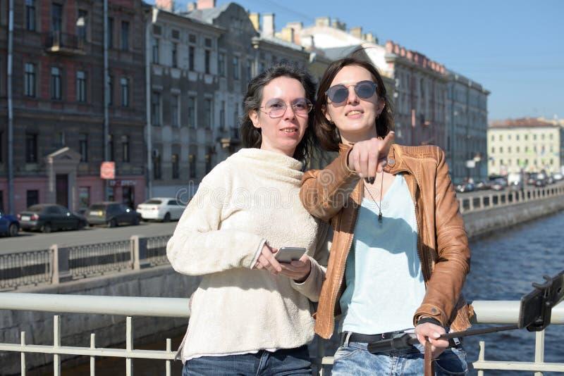 De jonge damestoeristen in Heilige Petersburg Rusland nemen selfies op een houten brug in het historische stadscentrum royalty-vrije stock foto's