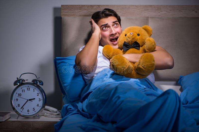 De jonge die man in bed wordt doen schrikken royalty-vrije stock foto