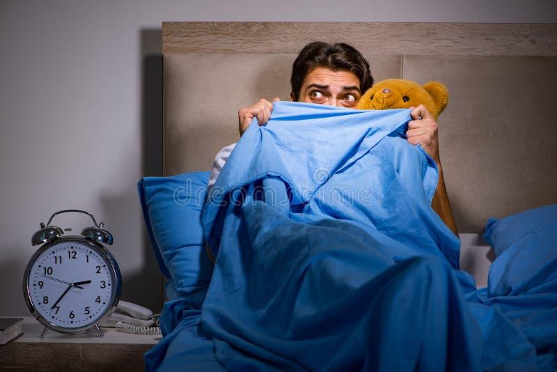 De jonge die man in bed wordt doen schrikken royalty-vrije stock afbeeldingen