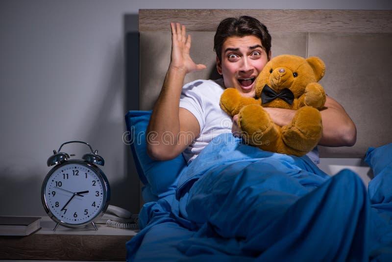 De jonge die man in bed wordt doen schrikken royalty-vrije stock foto's