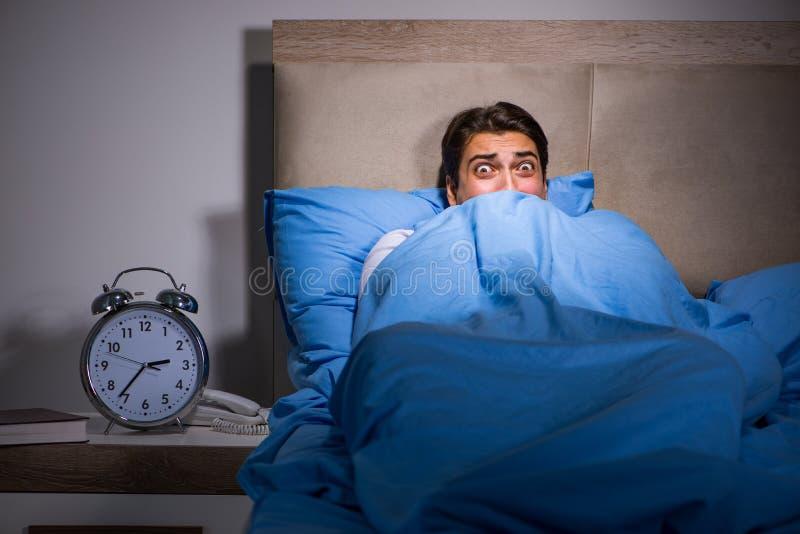 De jonge die man in bed wordt doen schrikken royalty-vrije stock fotografie