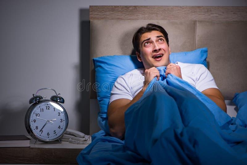 De jonge die man in bed wordt doen schrikken stock afbeelding